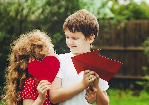 Enfants mignons tenant en forme de cœur rouge dans le parc de l'été.