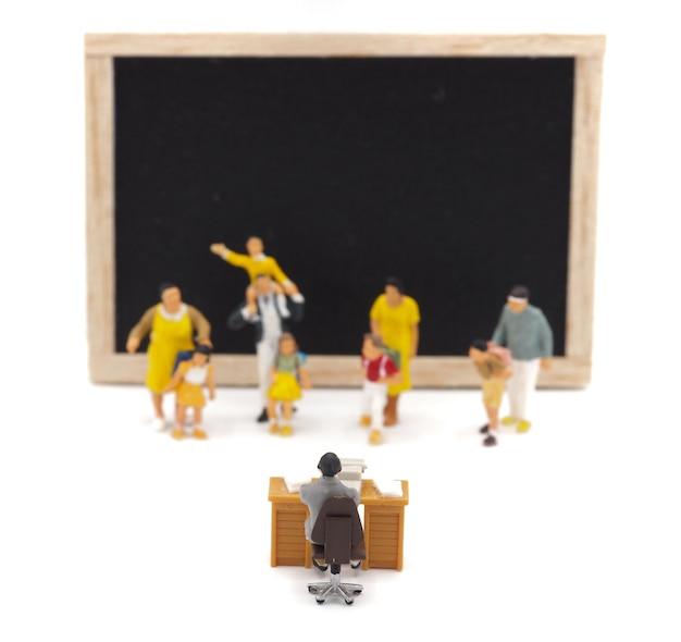 Enfants miniatures debout devant un tableau noir sur fond blanc. retour au concept de l'école.