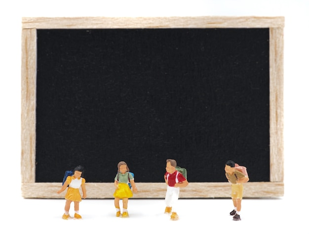 Enfants miniatures, debout devant un tableau noir sur fond blanc. retour au concept d'école.