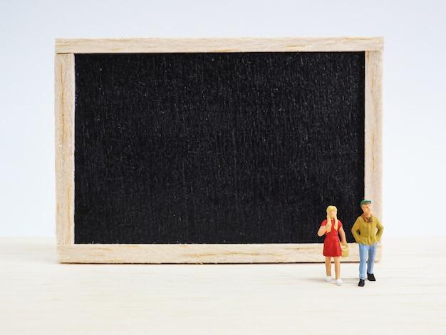 Enfants miniatures debout devant un tableau noir sur fond en bois. retour au concept de l'école.