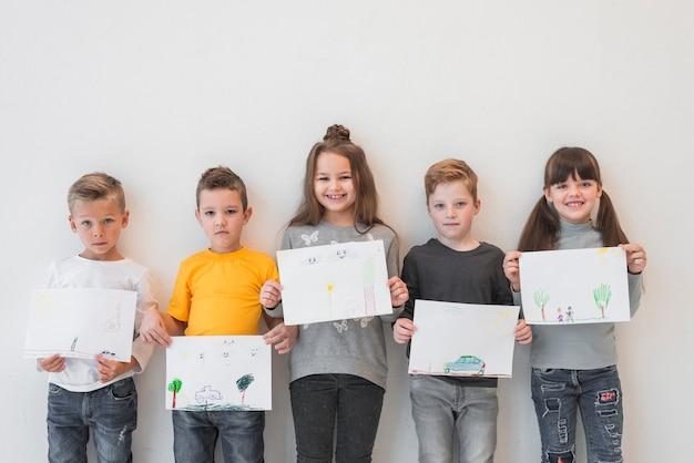 Enfants montrant leurs dessins