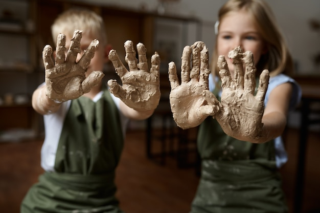 Les enfants montrent leurs mains recouvertes d'argile, les enfants en atelier. leçon à l'école des beaux-arts. jeunes maîtres de l'artisanat populaire, passe-temps agréable, enfance heureuse
