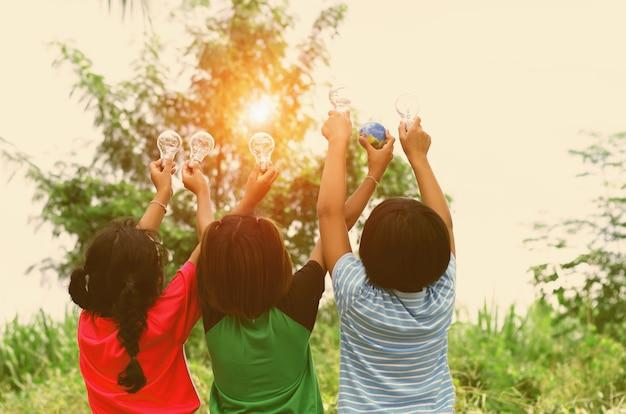 Les enfants montrent la main avec l'ampoule et le concept de jouet du monde l'énergie solaire