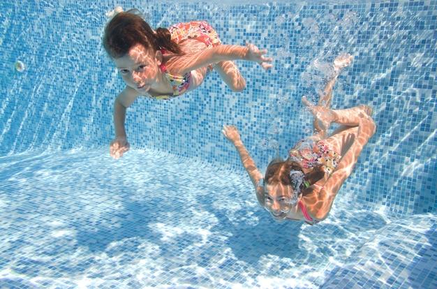 Les enfants nagent dans la piscine sous l'eau les petites filles actives s'amusent sous l'eau fitness pour enfants