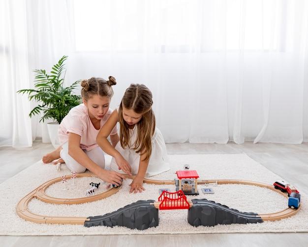 Enfants non binaires jouant avec un jeu de voitures à la maison