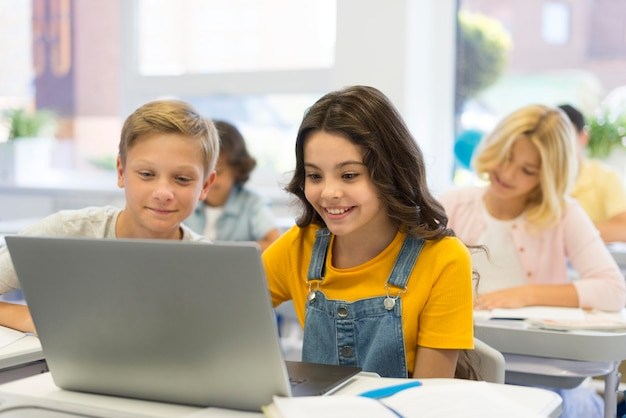 Enfants avec ordinateur portable à l'école