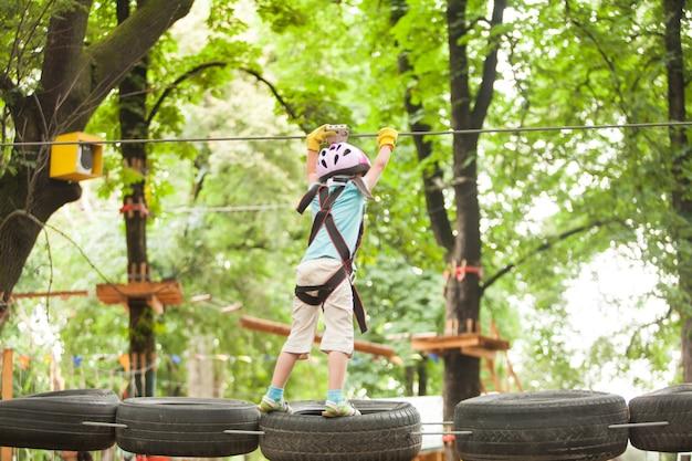 Enfants sur parcours d'obstacles dans le parc d'aventure en casque de montagne et équipement de sécurité