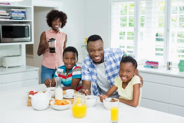 Enfants et parents prenant le petit déjeuner sur la table à la maison