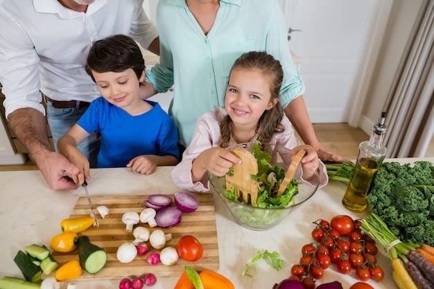 Enfants et parents préparent une salade de légumes dans la cuisine