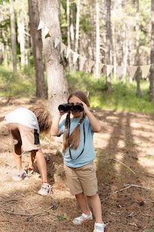 Enfants participant à une chasse au trésor dans une forêt