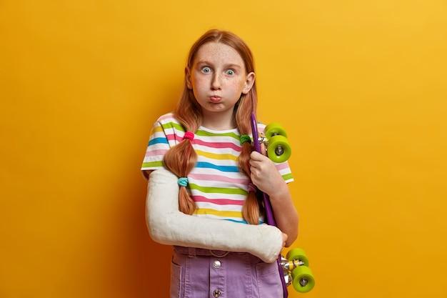 Enfants, passe-temps, concept de passe-temps. fille rousse souffle sur les joues et regarde, a la peau tachée de taches de rousseur pose avec des vêtements de skateboard moulés sur un bras cassé isolé sur un mur jaune. skateboard malchanceux