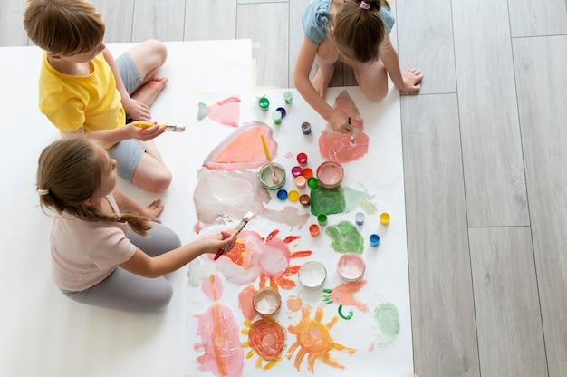 Enfants peignant ensemble en équipe