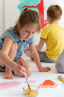 Enfants peignant ensemble se bouchent