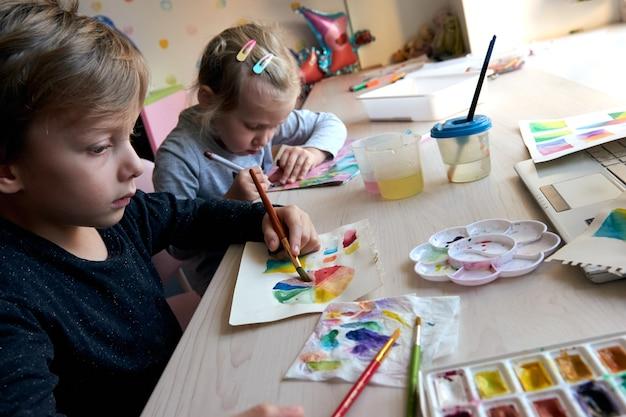 Enfants peignant des images avec des peintures à l'aquarelle pendant la leçon d'art. les élèves se concentrent sur le dessin au pinceau. roue et palette de couleurs d'aquarelle. cours de passe-temps pour débutants en théorie des couleurs