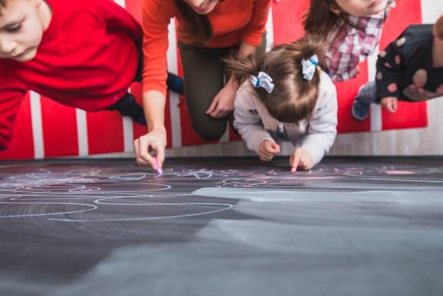 Enfants peignant sur tableau noir