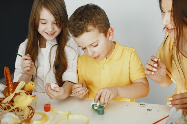 Les enfants peignent des œufs. mère enseigne aux enfants. assis à une table blanche.