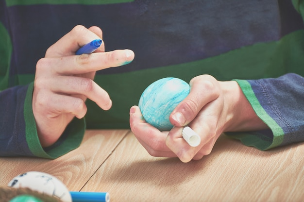 Des enfants peignent des œufs de pâques avec l'aide de leur mère et des marqueurs à la maison