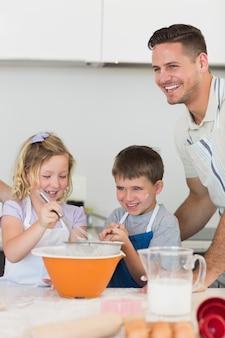 Enfants avec père, préparez des biscuits au comptoir