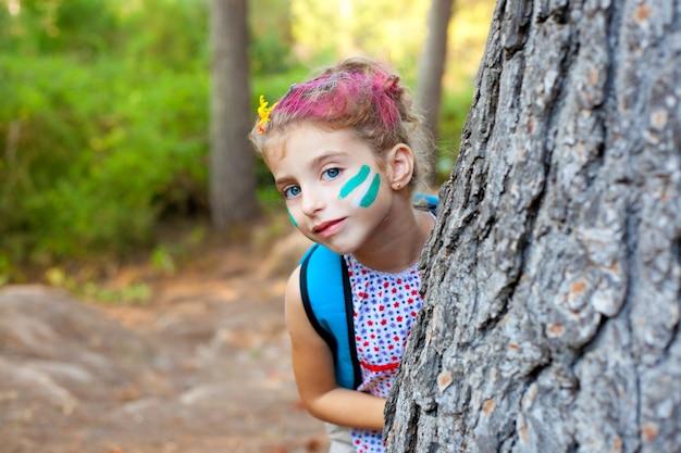 Enfants petite fille heureuse jouant dans l'arbre de la forêt