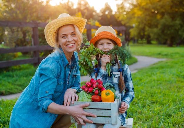 Enfants petite fille tenant maman un panier de légumes biologiques frais avec le jardin de la maison.