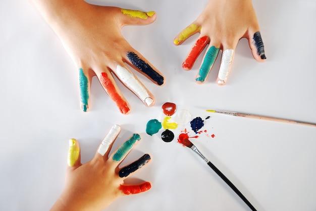 Enfants petites mains jouant avec des couleurs sur fond blanc