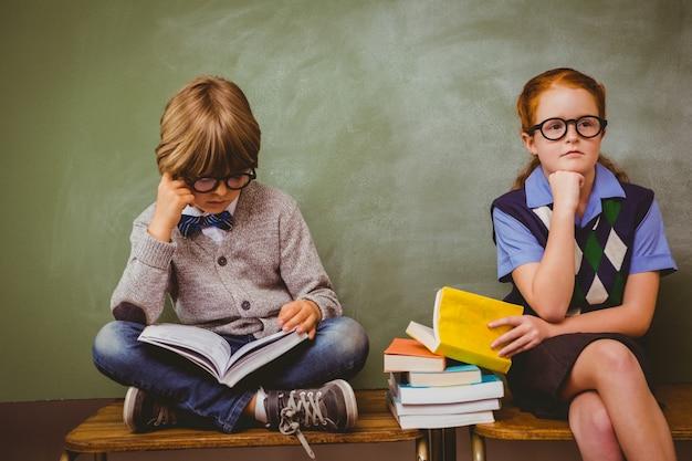 Enfants Avec Une Pile De Livres Dans La Salle De Classe Photo Premium