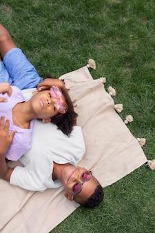 Enfants de plan moyen allongés ensemble sur une couverture