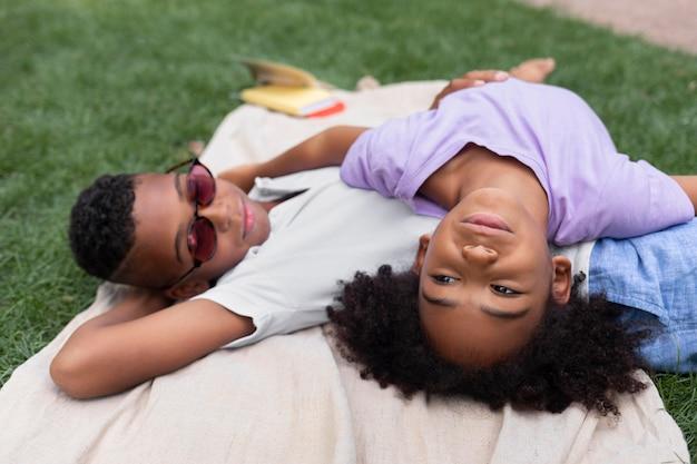 Enfants de plan moyen allongés ensemble
