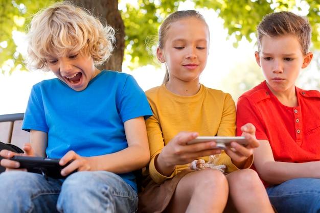 Enfants de plan moyen avec des appareils