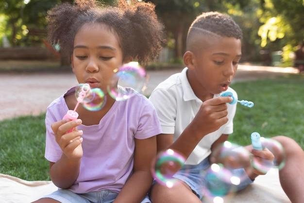 Enfants de plan moyen faisant des bulles de savon