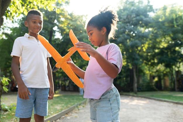 Des enfants à plan moyen jouant avec un avion