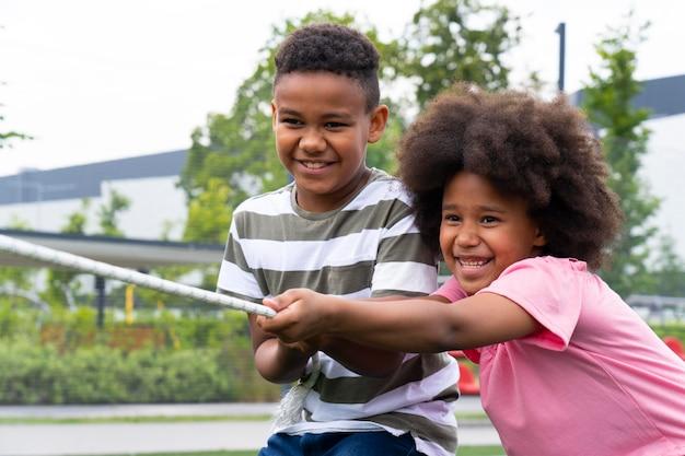 Enfants de plan moyen jouant avec une corde