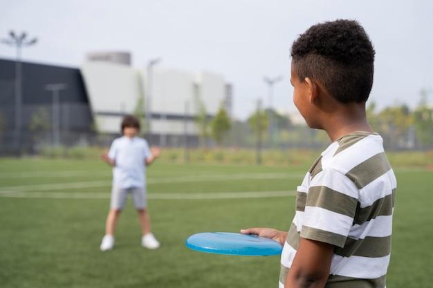 Enfants de plan moyen jouant avec le frisbee