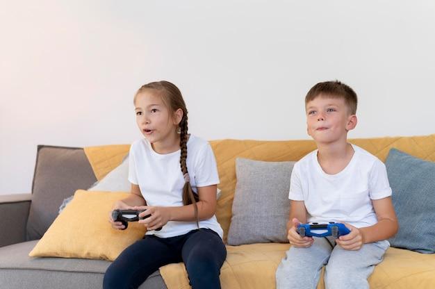 Des enfants à plan moyen jouant avec des manettes