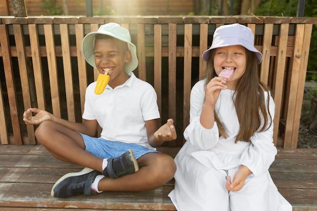 Enfants de plan moyen mangeant de la crème glacée