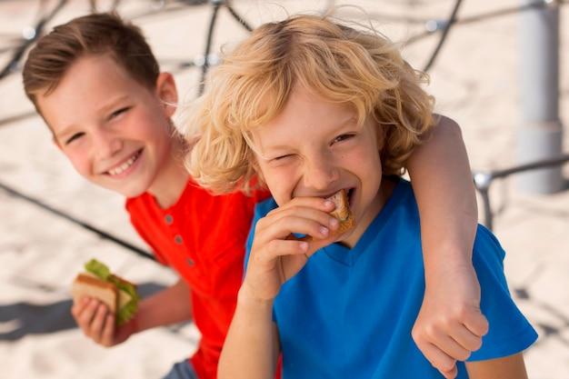 Enfants de plan moyen mangeant un sandwich