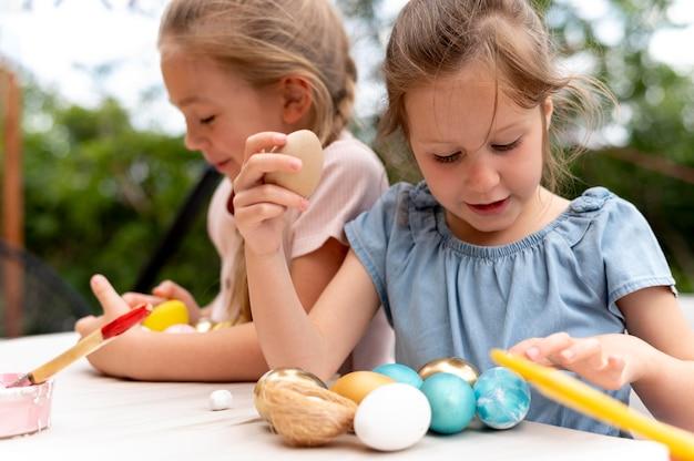 Enfants de plan moyen avec des œufs peints