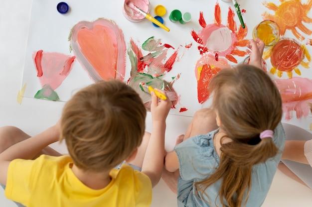 Enfants à plan moyen peignant ensemble