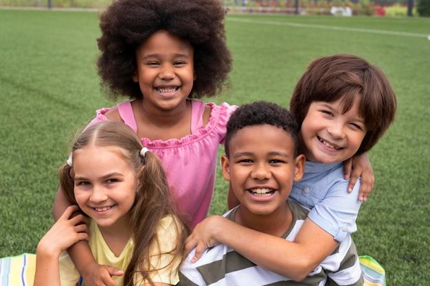 Enfants de plan moyen posant ensemble
