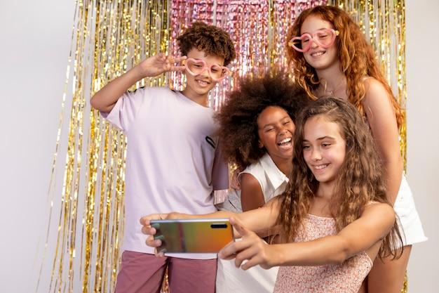 Des enfants à plan moyen prenant un selfie à la fête