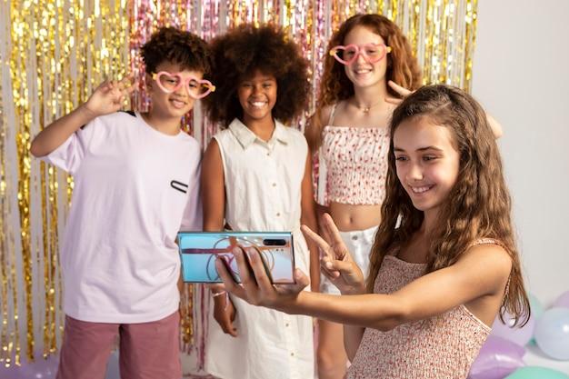 Des enfants à plan moyen prenant un selfie