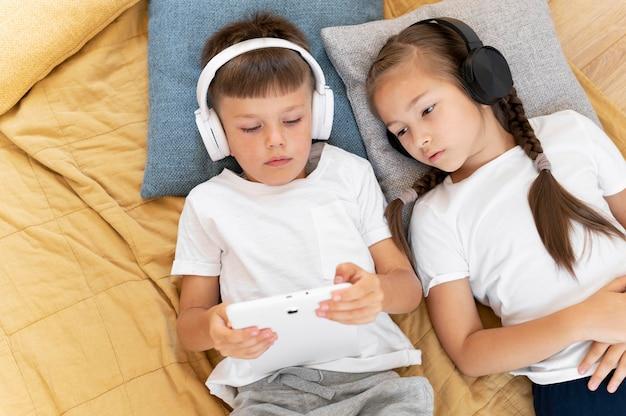 Enfants de plan moyen s'étendant avec des appareils