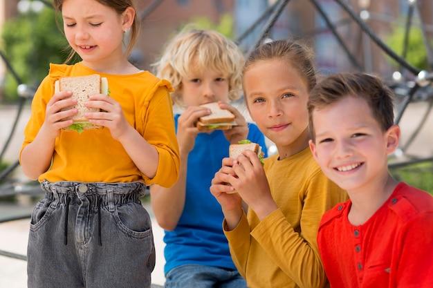 Enfants de plan moyen avec des sandwichs