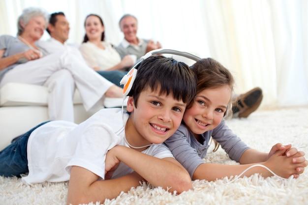 Enfants sur le plancher en écoutant de la musique dans le salon