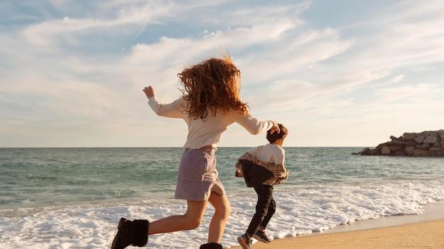Enfants en plein tir qui courent ensemble sur le rivage