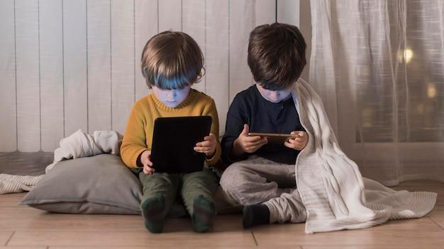 Enfants pleins tir assis avec des appareils