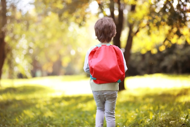 Enfants avec porte-documents pour une promenade dans le parc. vacances. le début des études des enfants.