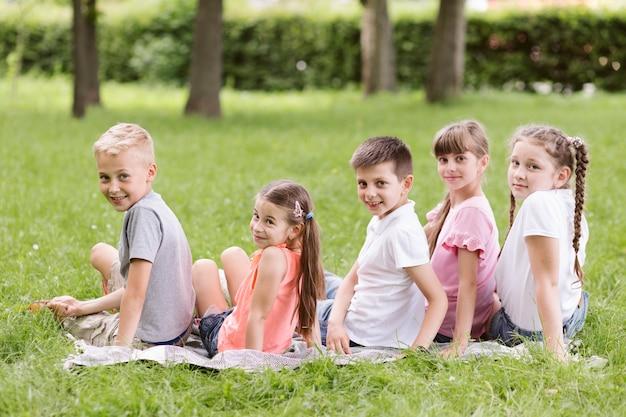 Enfants posant sur une couverture à l'extérieur