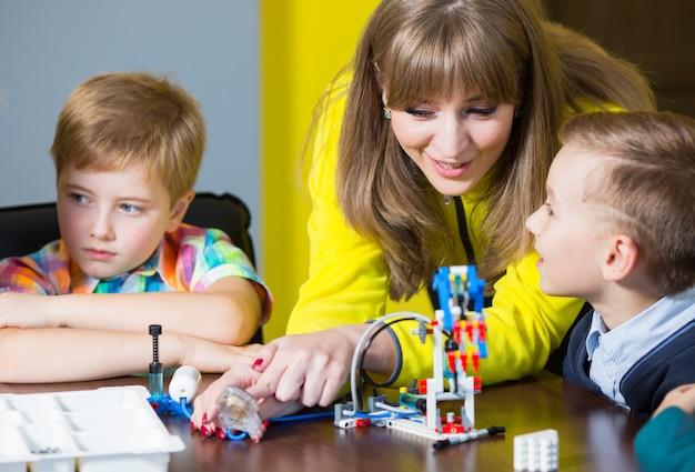 Les enfants positifs jouent et assemblent le constructeur dans la chambre des enfants.