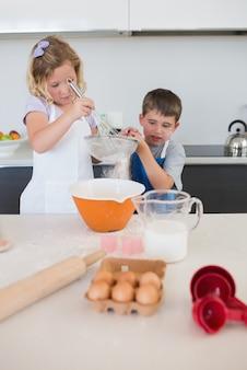 Enfants préparant des biscuits dans la cuisine